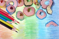 Kleurpotloden en spaanders potloden op een regenboogachtergrond Kleuren van regenboog stock afbeeldingen