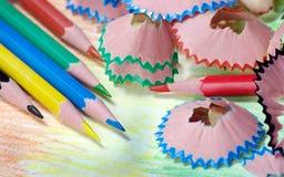 Kleurpotloden en spaanders potloden op een regenboogachtergrond Kleuren van regenboog stock afbeelding