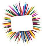 Kleurpotloden in het kader van een blad van document stock foto's