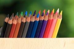 Kleurpotloden met een mand kennis op het gras royalty-vrije stock afbeeldingen