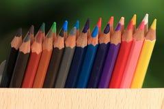 Kleurpotloden met een mand kennis op het gras stock foto
