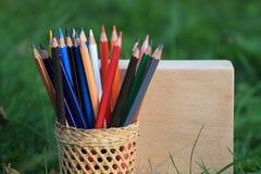 Kleurpotloden met een mand kennis op het gras royalty-vrije stock afbeelding