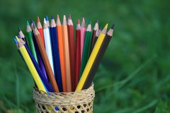 Kleurpotloden met een mand kennis op het gras stock afbeeldingen