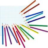 Kleurpotloden op een geregeld document Stock Foto's