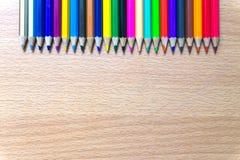 Kleurpotloden op een houten raad Stock Afbeeldingen