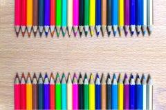 Kleurpotloden op een houten raad Stock Foto's