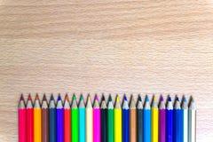 Kleurpotloden op een houten raad Royalty-vrije Stock Afbeeldingen