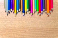 Kleurpotloden op een houten raad Stock Afbeelding