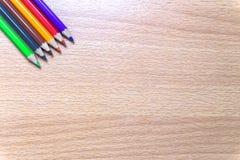 Kleurpotloden op een houten raad Stock Fotografie