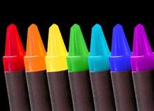 Kleurpotloden over zwarte Stock Foto's