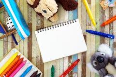 Kleurpotloden, speelgoed, leuke poppen met leeg open notitieboekje en kleurpotlood o stock afbeelding
