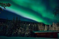 Kleurrijk aurora borealis over berg, bos en garage stock afbeeldingen