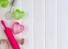 Kleurrijk bak hulpmiddelen voor koekje op witte houten achtergrond, hoogste mening stock afbeelding