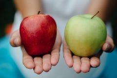Kleurrijk beeld van vrouwelijke handen met groene en rode appel Stock Foto