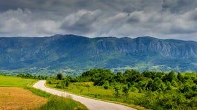 Kleurrijk berglandschap met lange weg en bewolkte hemel Royalty-vrije Stock Foto