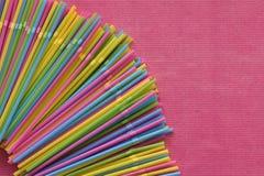 Kleurrijk beschikbaar plastic stro voor éénmalig gebruik in de hoek op de roze oppervlakte stock fotografie