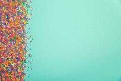 Kleurrijk bestrooit op rand van groene achtergrond stock foto