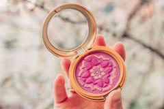 Kleurrijk bloos palet in vrouwelijke hand met vage achtergrond Fashinconcept royalty-vrije stock afbeeldingen
