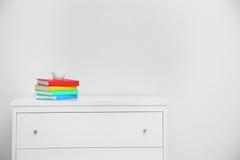 Kleurrijk boek op console witte lijst Kopkoffie op kleurrijk boek in woonkamer Stock Afbeelding