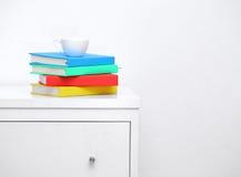 Kleurrijk boek op console witte lijst Kopkoffie op kleurrijk boek in woonkamer Stock Foto's