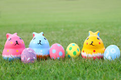 Kleurrijk ceramisch konijn drie met eieren op hoogste gras op Pasen Stock Foto's