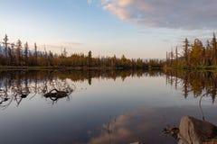 Kleurrijk de herfstbos door een stil meer met bezinningen van de hemel en de wolken Norilsk Talnakh royalty-vrije stock afbeelding