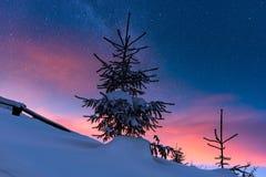 Kleurrijk de winter alpien landschap bij nacht met sterrige hemel en gloed van zonsondergang stock afbeeldingen