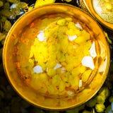 Kleurrijk die bloembloemblaadjes en water met parfum in gouden worden gemengd Stock Fotografie