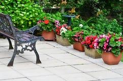 Kleurrijk Engels terrasgebied met planters en ijzerbank stock afbeelding