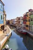 Kleurrijk geschilderd huizen en kanaal met boten op Burano-eiland, Italië Stock Foto