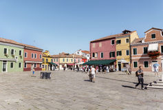 Kleurrijk geschilderd huizen en vierkant met mensen op Burano-eiland, Italië Royalty-vrije Stock Foto's