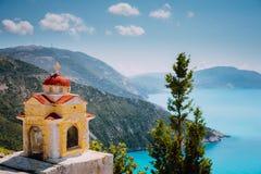 Kleurrijk heiligdom Proskinitari op voetstuk Verbazende overzeese mening aan de kustlijn van Griekenland op de achtergrond stock afbeeldingen