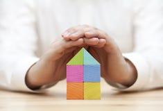 Kleurrijk houten die blokhuis door handen wordt beschermd Royalty-vrije Stock Foto's