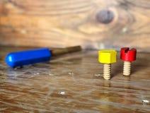 Kleurrijk houten stuk speelgoed Rode en gele noten en blauwe schroevedraaier op de uitstekende houten lijst Stock Afbeeldingen