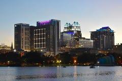 Kleurrijk iluminated gebouwen, groene bos en zwaanboten in Eola-Meerpark in Orlando Downt stock foto