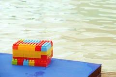Kleurrijk jonge geitjesspeelgoed door de kant van zwembad stock afbeelding