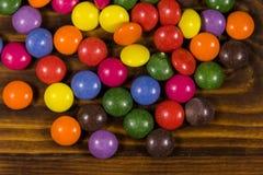 Kleurrijk knoop gevormd die suikergoed met chocolade op houten lijst wordt gevuld stock foto's