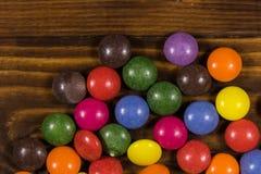 Kleurrijk knoop gevormd die suikergoed met chocolade op houten lijst wordt gevuld stock fotografie