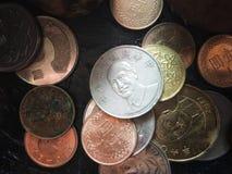 Kleurrijk oud muntstuk die op zwarte houten lijst stapelen royalty-vrije stock foto's