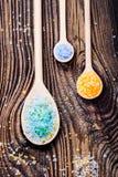 Kleurrijk overzees zout in houten lepels gezet op oude houten lijst Royalty-vrije Stock Afbeeldingen