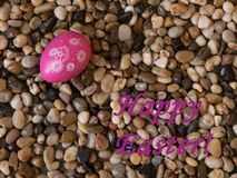 Kleurrijk paasei op bed van strand pebbes met Gelukkige Pasen-groet Royalty-vrije Stock Foto