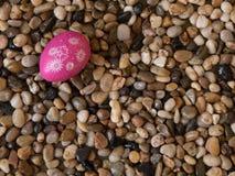 Kleurrijk paasei op bed van strandkiezelstenen Royalty-vrije Stock Foto's