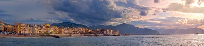 Kleurrijk panorama van de kustlijn van Sicilië met bewolkte zonsonderganghemel Stock Foto