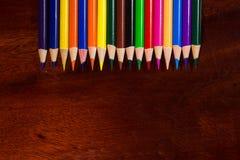 Kleurrijk pastelkleurkleurpotlood op oud bureau Royalty-vrije Stock Afbeelding
