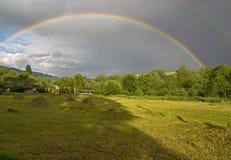 Kleurrijk regenboogrecht onder vlakte in oude grote bergen Stock Fotografie
