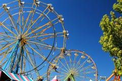 Kleurrijk Reuzenrad twee in silhouet tegen een heldere blauwe de zomerhemel met bomen aan één kant royalty-vrije stock fotografie