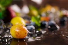 Kleurrijk rijp bessenclose-up Heldere zoete druiven, bosbessen en aardbeien met verse munt en de donkere chocoladesaus Stock Foto