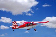 Kleurrijk rood vliegtuig tijdens de vlucht Stock Afbeeldingen