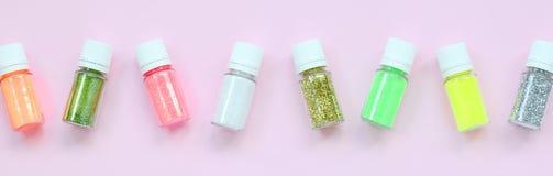 Kleurrijk schittert leugens op pastelkleur roze achtergrond Vele ronde kruiken met multi-colored heldere fonkelingen voor nagella royalty-vrije stock afbeeldingen