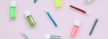Kleurrijk schittert leugens op pastelkleur roze achtergrond Vele ronde kruiken met multi-colored heldere fonkelingen voor nagella stock fotografie